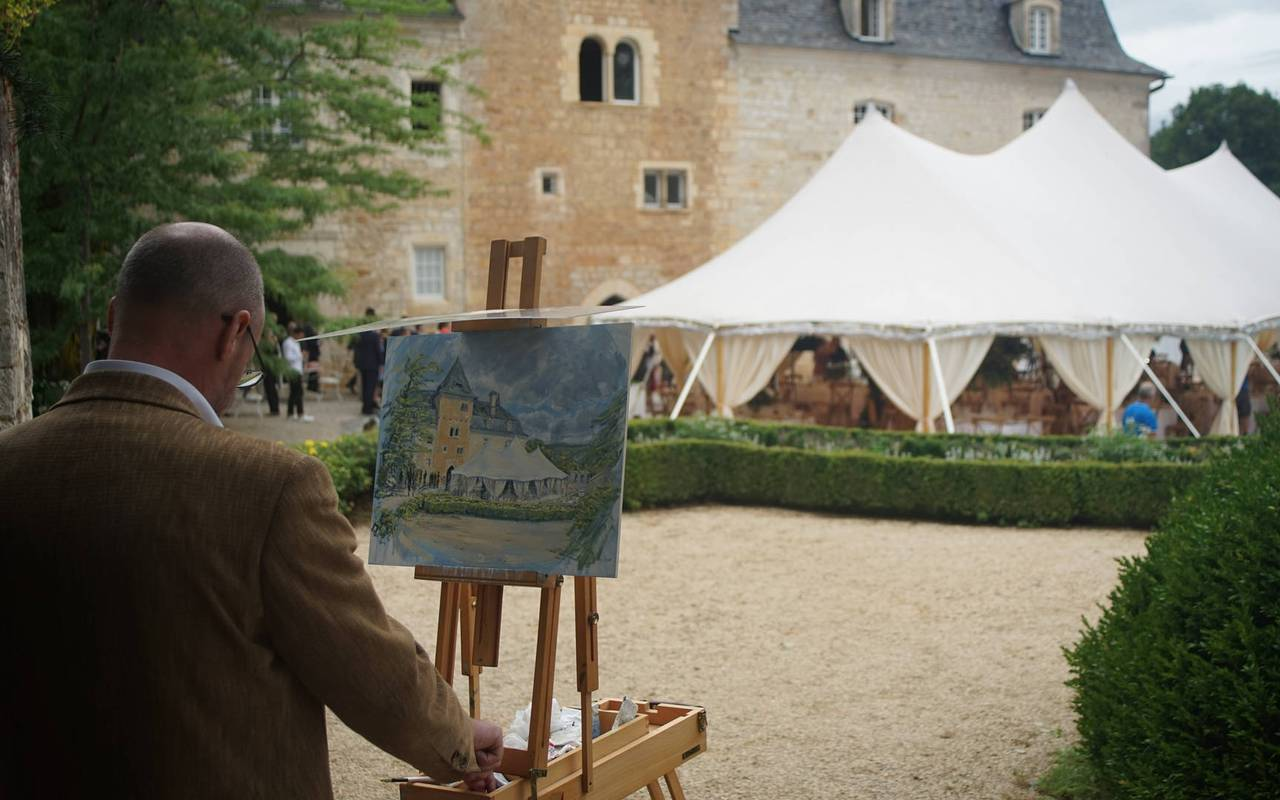 Man painting a canvas in castle courtyard - chateau hotel dordogne