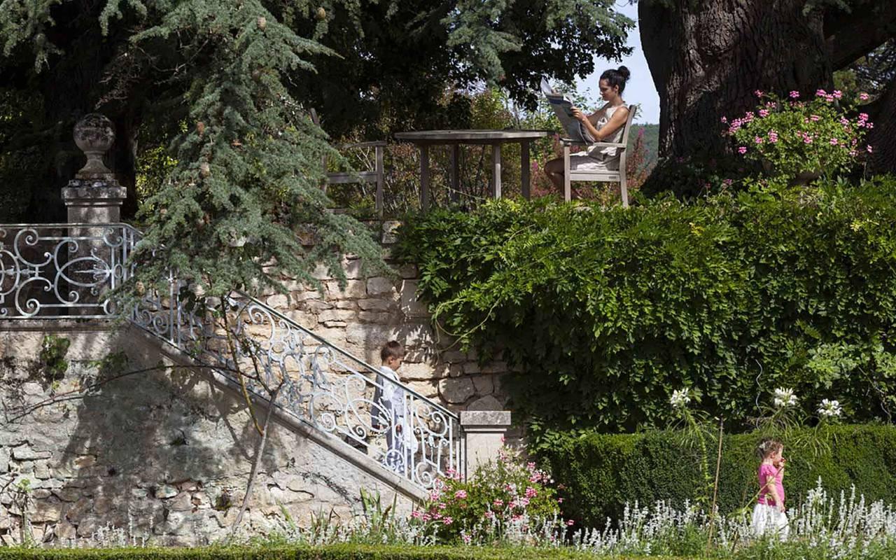 Femme en train de lire dans le parc du chateau de la treyne - hotel lot