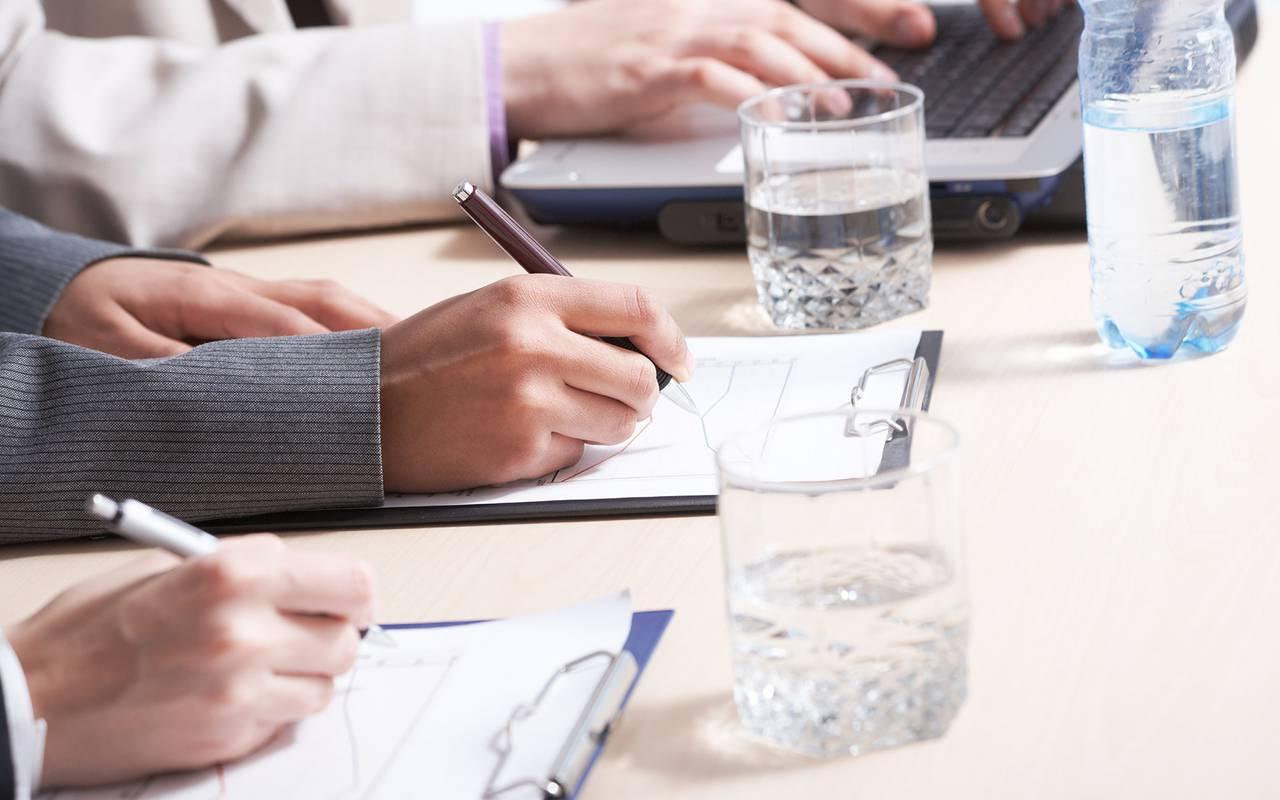 Personnes écrivant sur une feuille pendant une réunion - hotel rocamadour